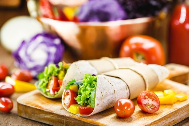 Two vegetarian tortilla wraps on wooden cutting board with vegetables in the surface