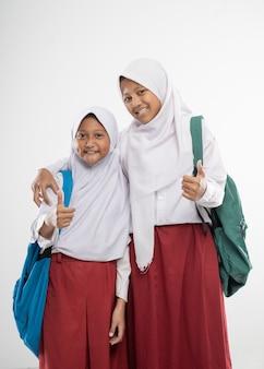 배낭과 책을 들고 엄지 손가락으로 초등학교 교복을 입은 두 명의 가려져있는 소녀