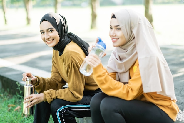 Two veiled girls sitting enjoy drinking water with bottle after doing outdoor sports together the garden field