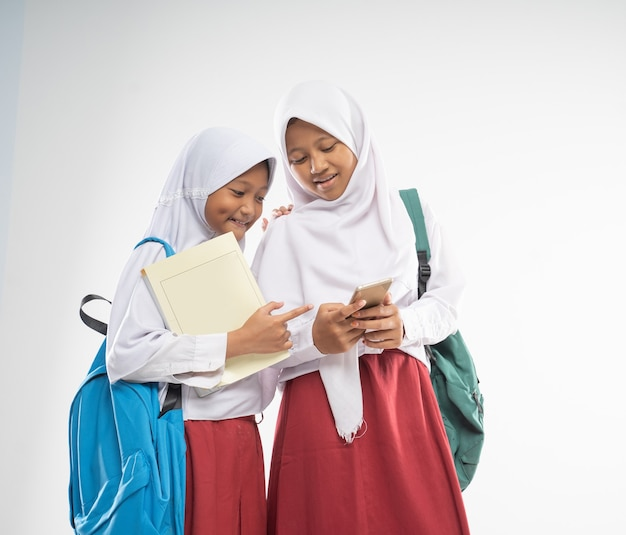 Two veiled girls wearing elementary school uniforms while using a mobile phone together with a backp...