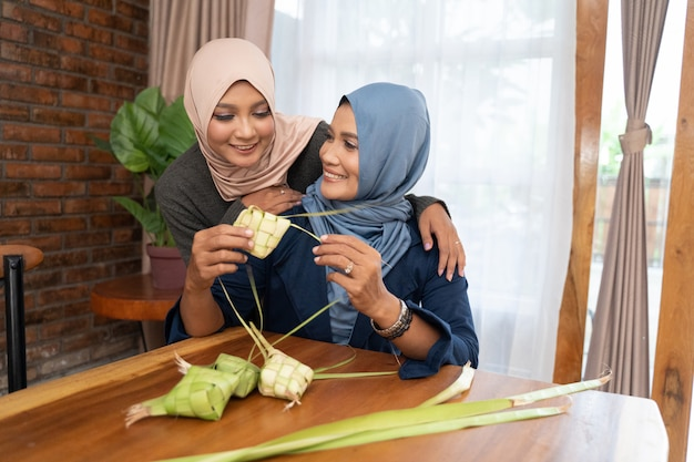 Two veiled woman make a woven wrapper of ketupat