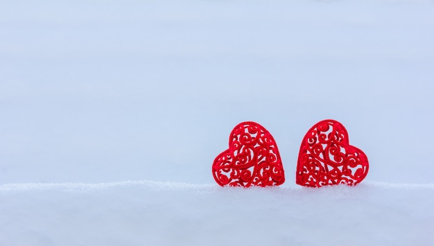 Two velvet heart in a snowdrift on a snowy background with copy space, valentine's day card