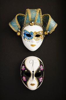 Two venetian carnival masks on the black surface. location vertical.