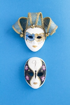 Two venetian carnival masks on the blue surface. top view. location vertical.