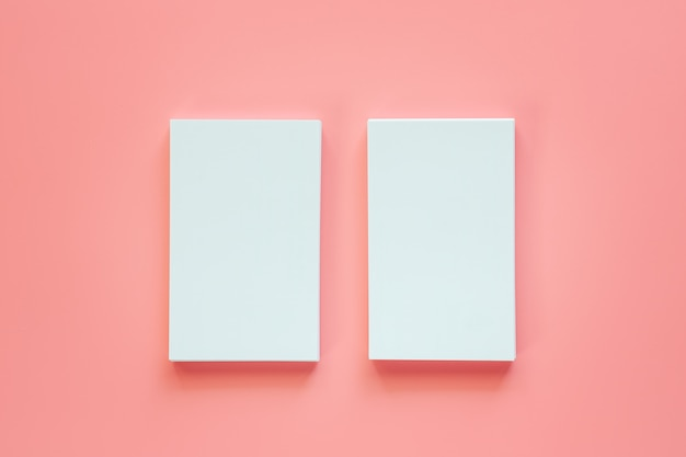 Two vertical of blank business cards on pink background