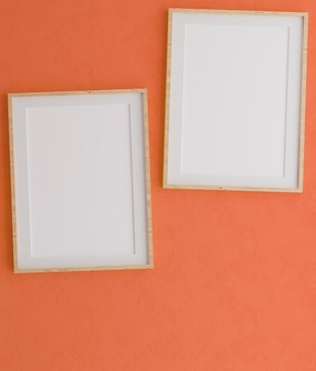 Two vertical wooden frames on orange wall