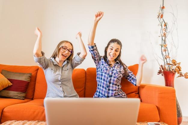 自宅のソファに座っているノートパソコンの画面を見ながら手を上げて応援している2人の非常に幸せな女の子。仕事で成功している若い勝者の女性。あなたの人生を変えて、より良く生きるために好ましい仕事をしてください