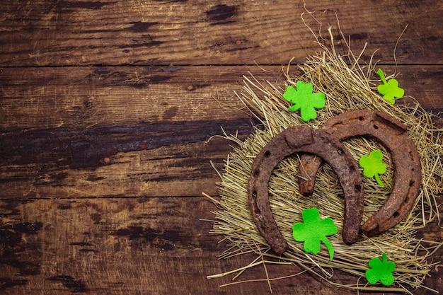 干し草に2つの非常に古い鋳鉄金属の馬の蹄鉄、クローバーは葉を感じた。幸運のシンボル、聖パトリックの日の概念。アンティークの木製の背景、馬のアクセサリー