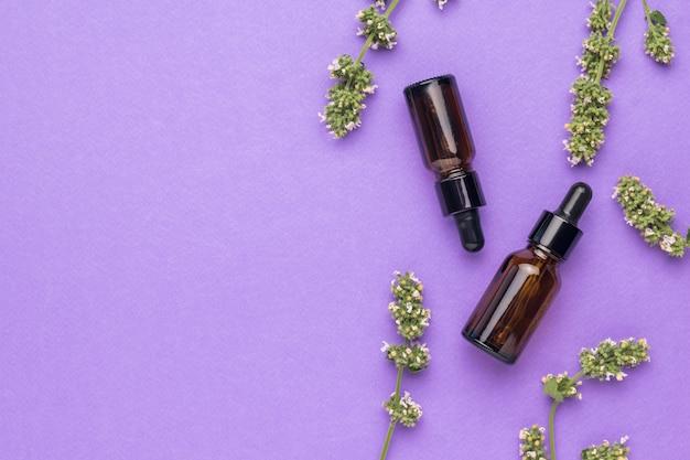 Два флакона с лекарственным раствором и лекарственными травами на фиолетовом фоне. концепция лечения и ухода за телом с помощью натуральных средств. плоская планировка.