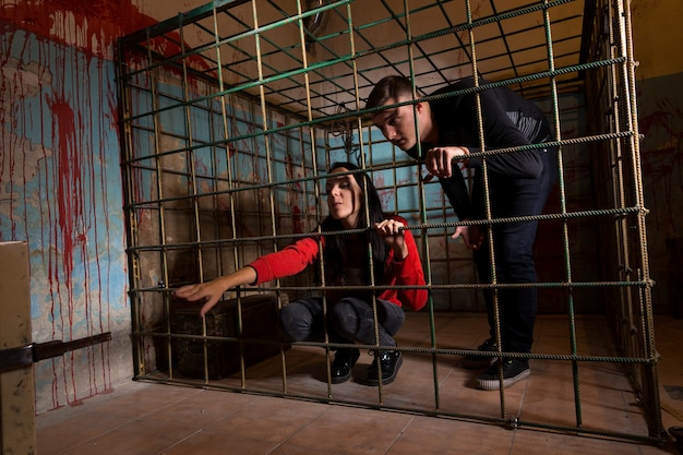 Two victims imprisoned in a metal cage with a blood splattered wall behind them, girl pulling her hand through the bars and trying to get out