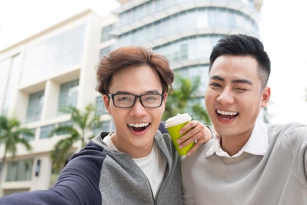外国の都市で自撮りをする 2 人のベトナム人男性旅行者