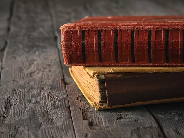 暗い木製のテーブルに2冊のヴィンテージ本。過去の文学。