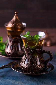 暗い背景に新鮮なお茶と緑のミントの小枝を入れたブロンズカップホルダーに2つのビンテージグラス。