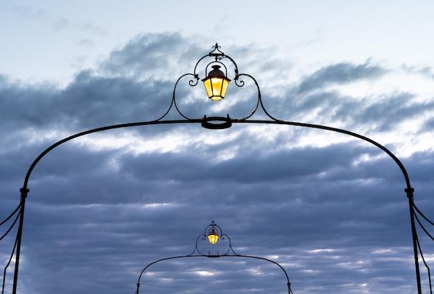 Два старинных уличных фонаря горят в драматическом вечернем небе