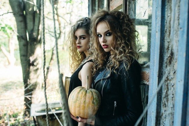 Two vintage women as witches, posing beside an abandoned building on the eve of halloween
