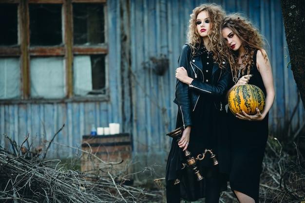 Две винтажные женщины в образе ведьм позируют перед заброшенным домом накануне хэллоуина
