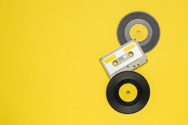 두 개의 비닐 디스크와 노란색 벽에 자기 테이프가있는 카세트. 오디오 녹음을 저장하고 재생하기위한 레트로 장치.