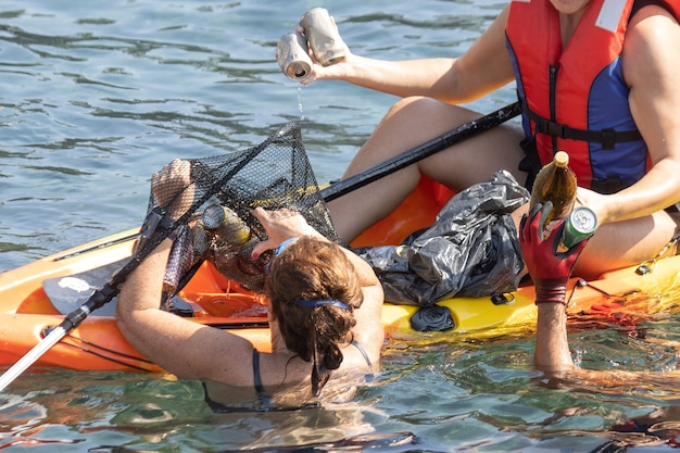 Двое волонтеров собирают мусор и пластик в море