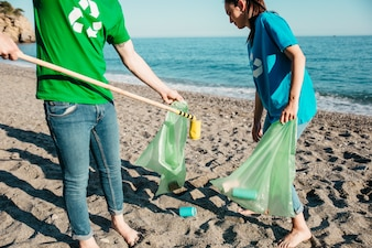 Two volunteers collecting waste at the beach