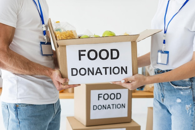 Два волонтера держат коробку для пожертвований еды