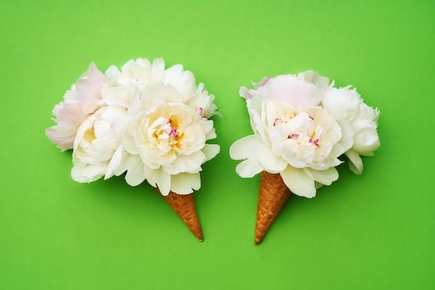 Два вафельных рожка мороженого с белыми цветами пиона на зеленом столе. летняя концепция. копировать пространство