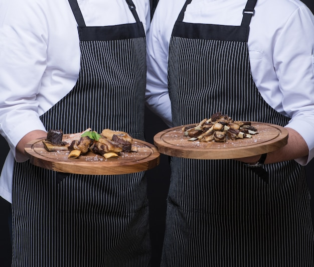 Two waiters serve a meat dish on a wooden tray