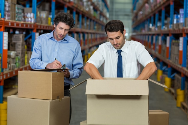 Two warehouse workers checking the boxes