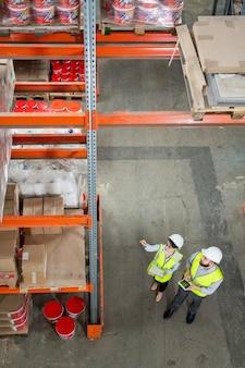 Двое складских рабочих в униформе обсуждают качество доставленных товаров