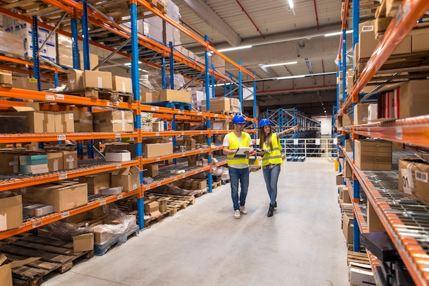 Two warehouse workers walking in distribution storage area discussing about logistics and organization