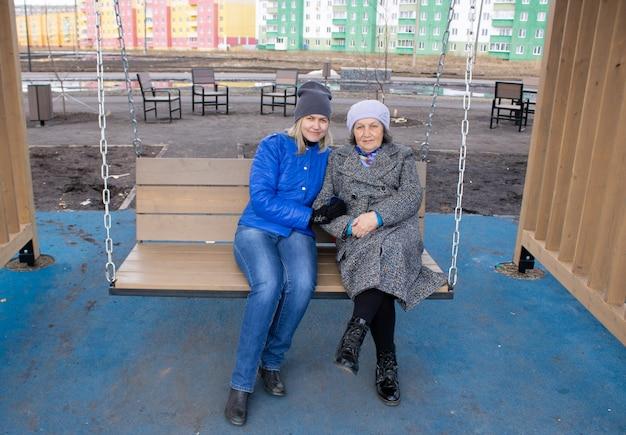 따뜻하게 차려입은 두 여성이 그네에 앉아 있다 노모의 손을 잡고 있는 여성