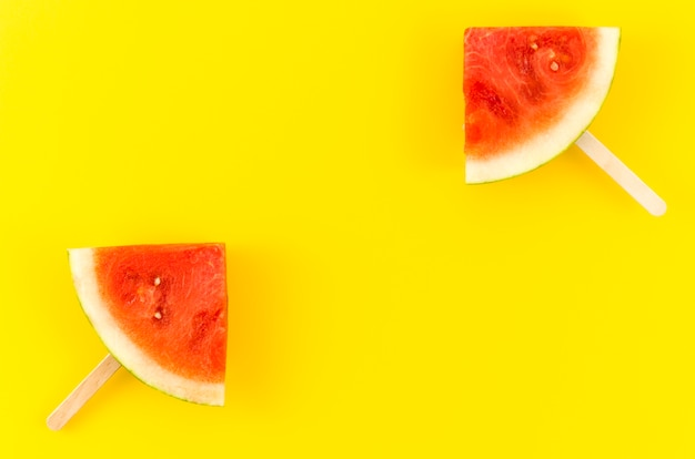 Two watermelon slice popsicles on yellow table