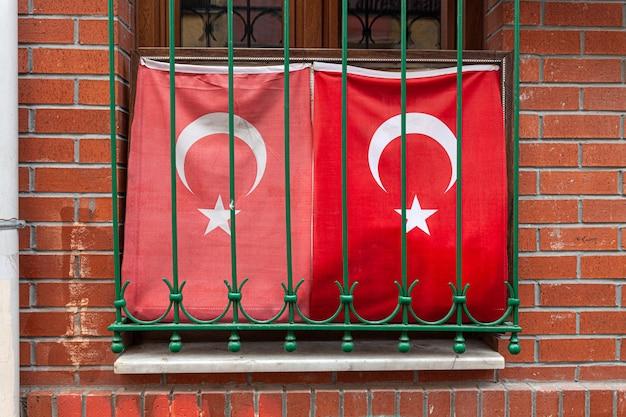 Два развевающихся турецкого флага в окне с решетчатой кирпичной стеной