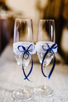 Two wedding glasses are decorated with blue ribbons and hearts.