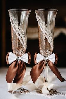 Два свадебных бокала украшены коричневыми лентами.