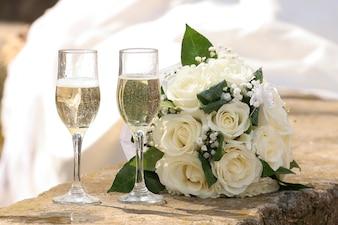 シャンパンと白いバラの花束を2つの結婚式のメガネ