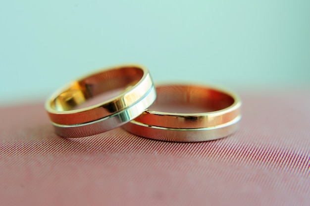 Two wedding gold rings in blurred background