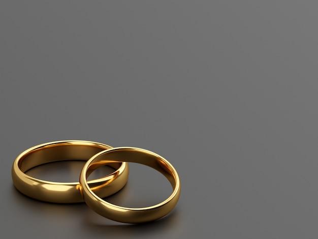 두 개의 결혼 금 반지는 회색 배경에 나란히 놓여 있습니다.