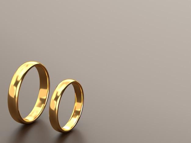 두 개의 결혼 금 반지가 회색 테이블에 나란히 놓여 있습니다.
