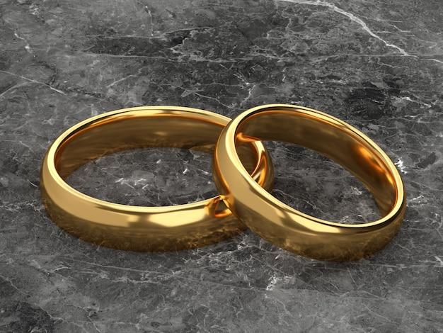 두 개의 결혼 금 반지는 대리석 배경에 나란히 놓여 있습니다.