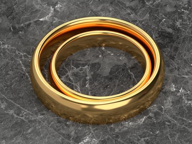 두 개의 결혼 금 반지가 대리석 테이블에 나란히 놓여 있습니다.