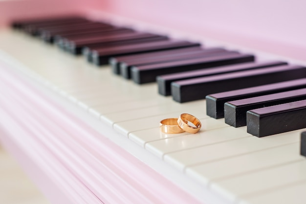 Two wedding gold rings on the piano