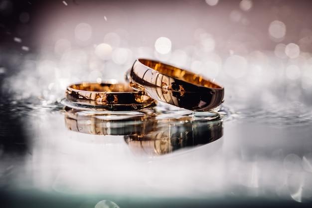 平らな面の上に敷設水しぶきで2つの結婚式ゴールデンリング