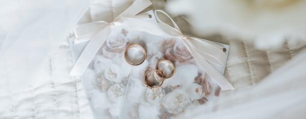 Два обручальных кольца и помолвочное кольцо лежат на приглашении с поверхностью цветов