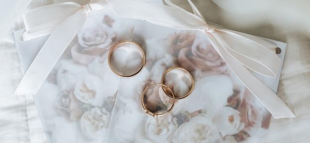 Два обручальных кольца и обручальное кольцо лежат на стене приглашения с цветами
