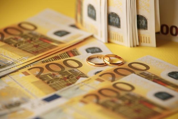 Два обручальных кольца и деньги как символ дорогого союза