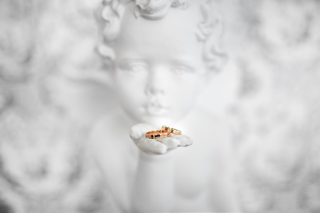 Two wedding rings in angel hand, close up photo