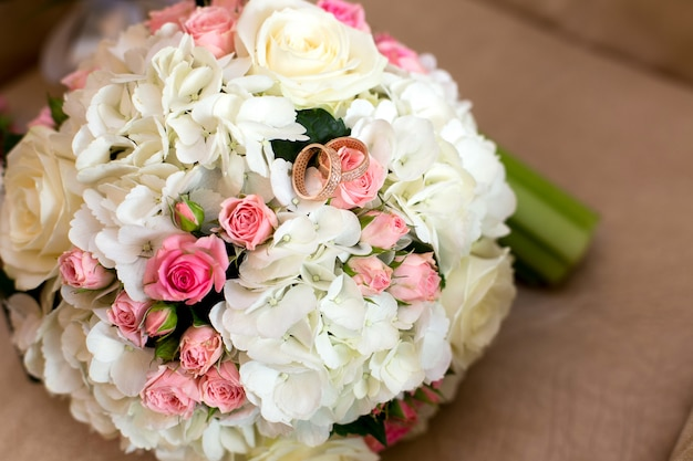 Two wedding rings at a bouquet of red and white roses