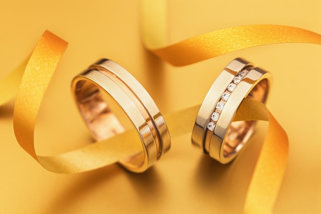 Two wedding rings connected by a ribbon on a yellow surface