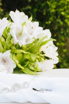 Two wedding rings and crown on scarf with beautiful flower bouquet over table