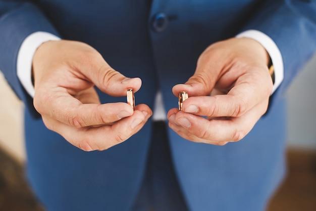 Два обручальных кольца в руке жениха